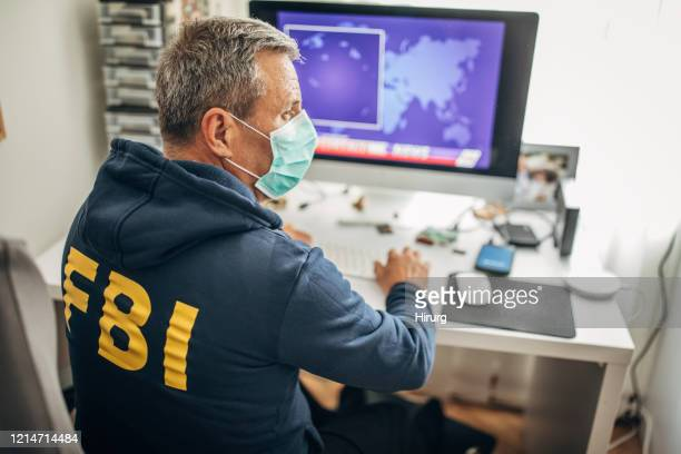 senior fbi agent with protective mask working in the office - fbi stock pictures, royalty-free photos & images