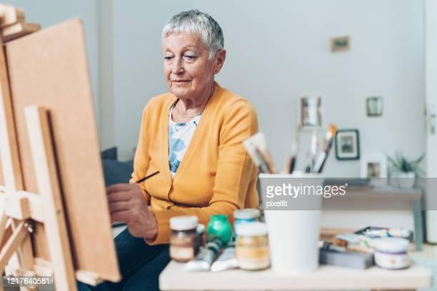 hogere vrouwelijke kunstenaar die aan een het schilderen werkt - linkshandig stockfoto's en -beelden