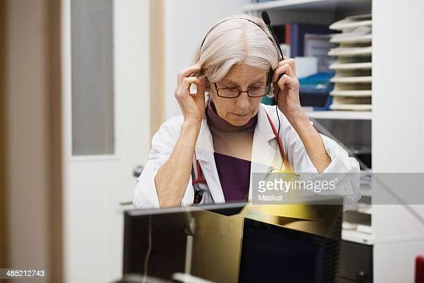 Senior female audiologist wearing headphones in examination room