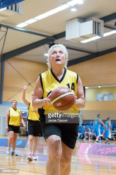 Senior female basketball player in action on court with ball