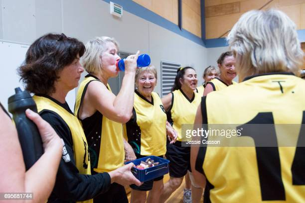 Senior female basketball players have team talk on indoor court