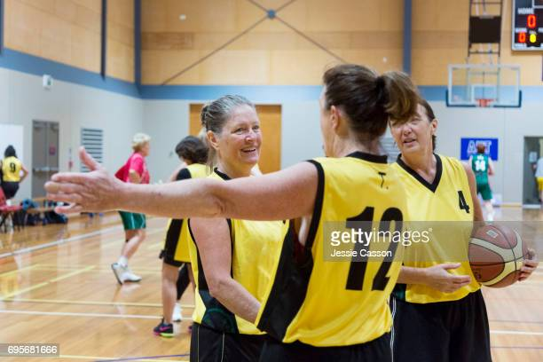 Senior female basketball players on court, one player giving direction to another player