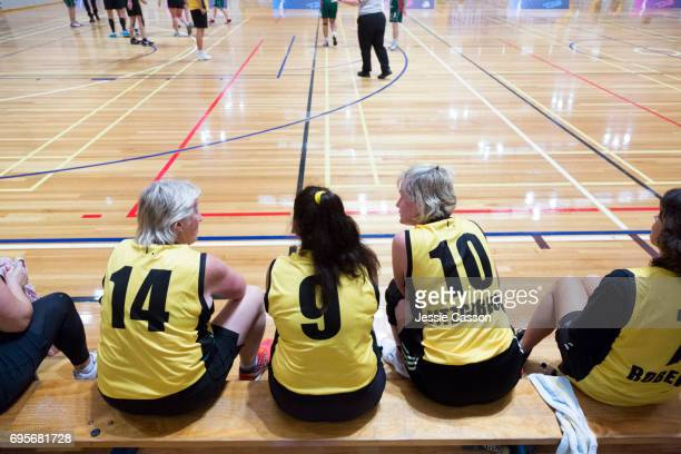 Senior female basketball players sit inside on bench beside court watching the match