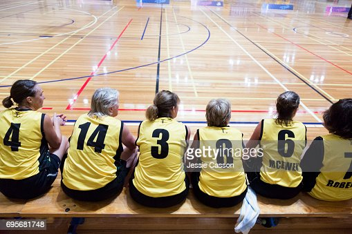 Senior female basketball players sit on bench beside court watching the match