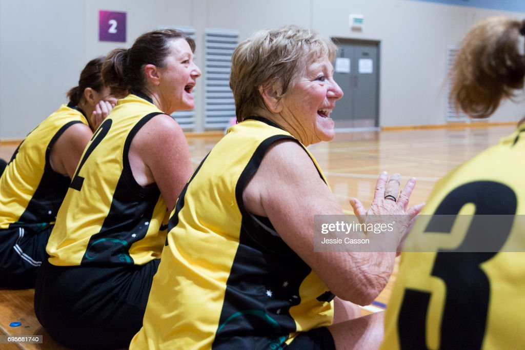 Senior female basketball players sit on bench celebrating beside court : Stock Photo
