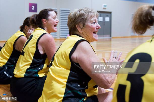 Senior female basketball players sit on bench celebrating beside court