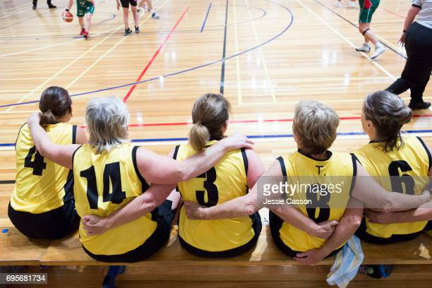 Senior female basketball players sit on bench with arms around each other beside court watching the match