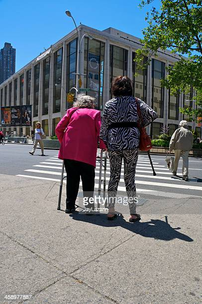 Senior female being helped to cross intersection, Broadway, NYC