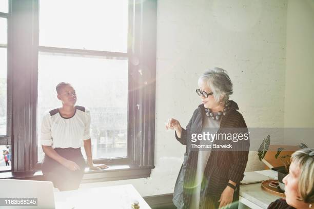senior female business owner leading meeting with employees in office - working seniors stock pictures, royalty-free photos & images