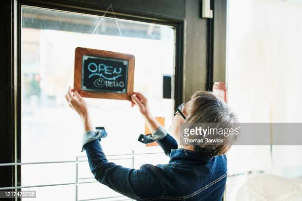 senior female business owner turning open sign on door before opening boutique - kleinunternehmen stock-fotos und bilder