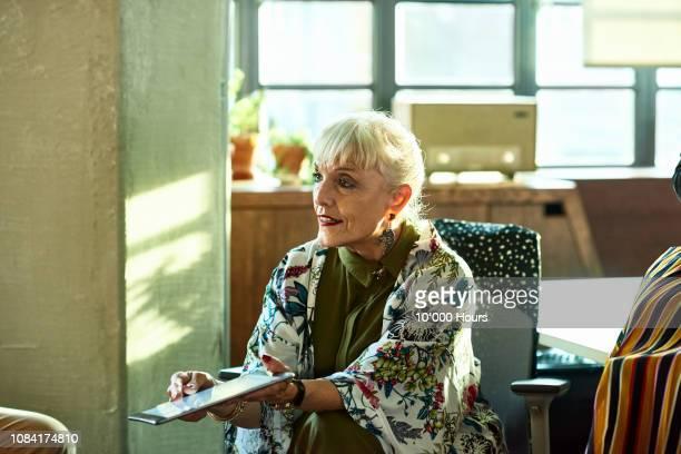 Senior female businesswoman showing digital tablet in meeting