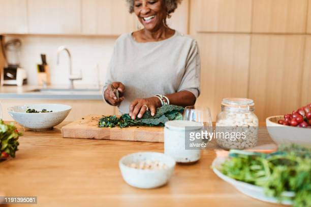 senior female chopping vegetable at kitchen island - healthy eating stock pictures, royalty-free photos & images