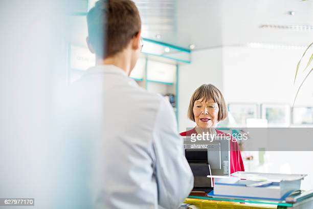 Senior female customer buying medicine in pharmacy