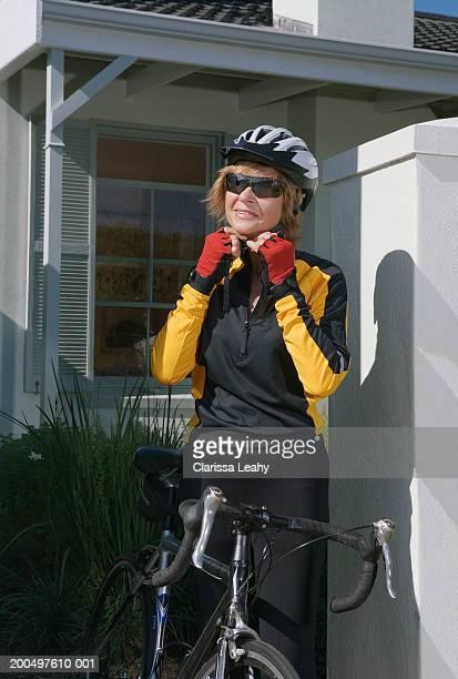 Senior female cyclist adjusting helmet at front gate of house
