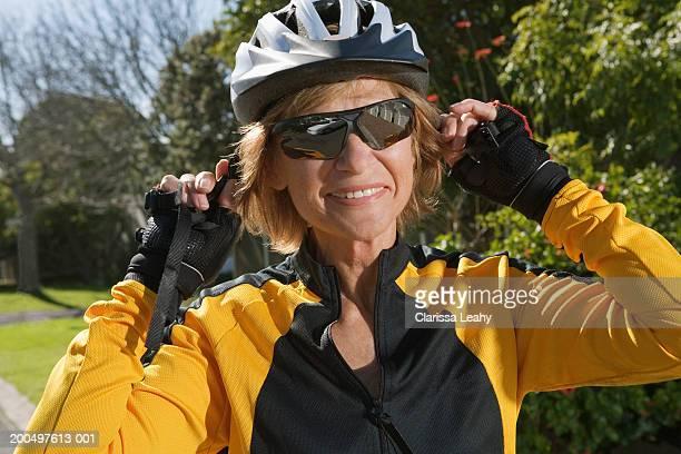 Senior female cyclist putting on helmet, smiling, close-up