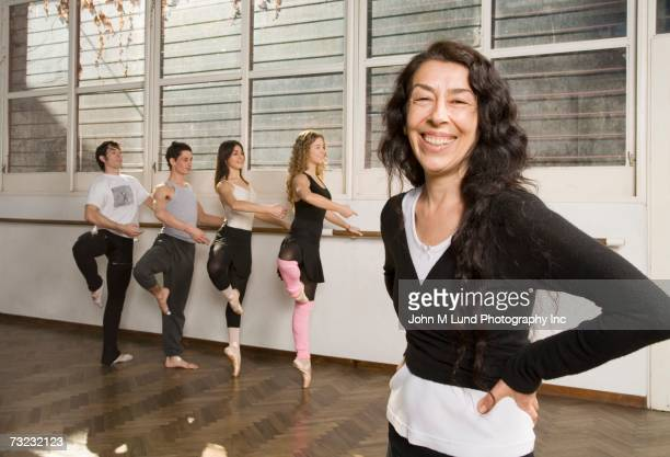 Senior female dance teacher smiling with students in background