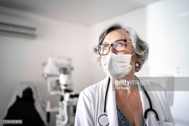 senior female doctor at hospital using protective mask - eye doctor stock pictures, royalty-free photos & images