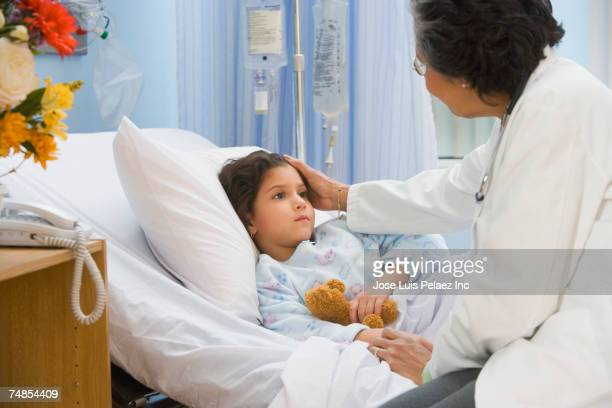 senior female doctor checking on girl in hospital bed - girl in hospital bed sick stock photos and pictures