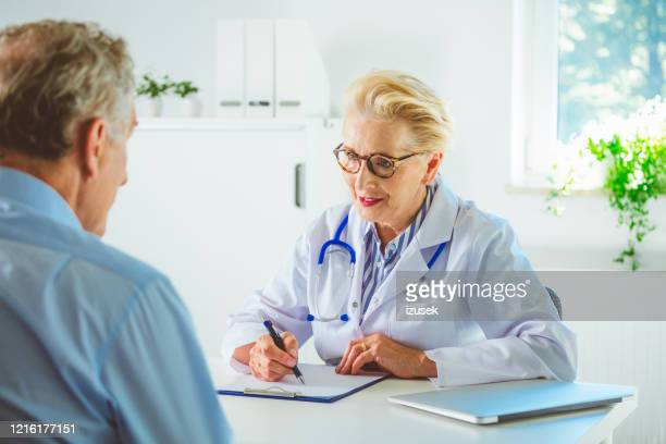senior female doctor discussing with man in her office - outpatient care stock pictures, royalty-free photos & images