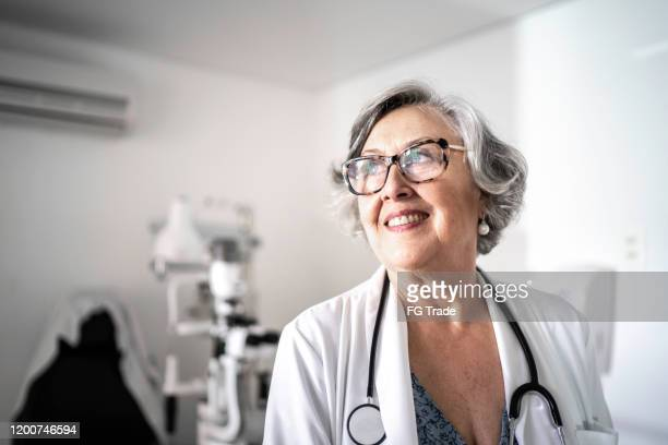 senior female doctor dreaming / contemplation at hospital - female doctor stock pictures, royalty-free photos & images