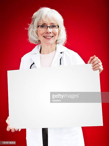 senior female doctor holding a blank sign - white hair stock pictures, royalty-free photos & images