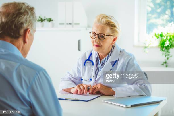 senior female doctor in her office - outpatient care stock pictures, royalty-free photos & images