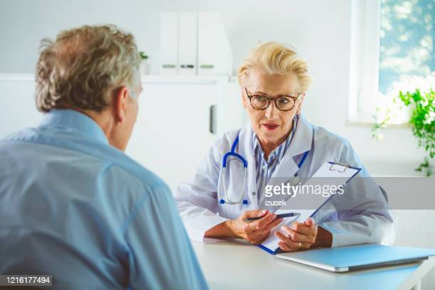 senior female doctor showing medical test results on clipboard - outpatient care stock pictures, royalty-free photos & images