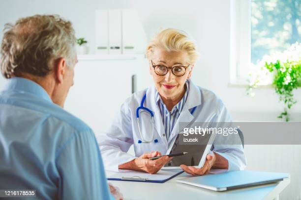 senior female doctor showing medical test results on digital tablet - outpatient care stock pictures, royalty-free photos & images