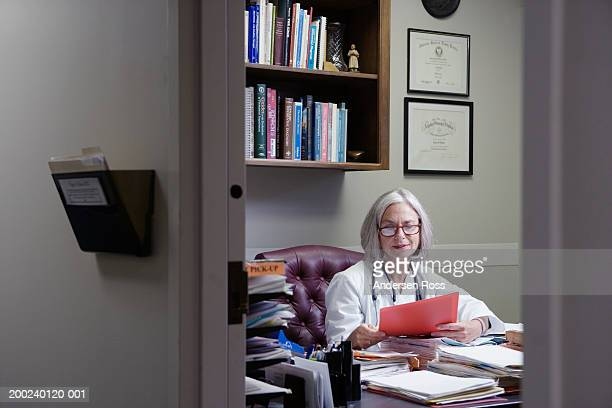 Senior female doctor sitting at desk in office, reading medical file