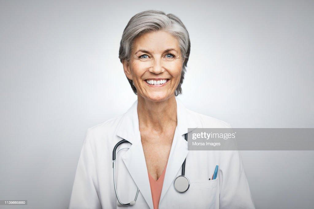 Senior female doctor smiling on white background : Stock-Foto
