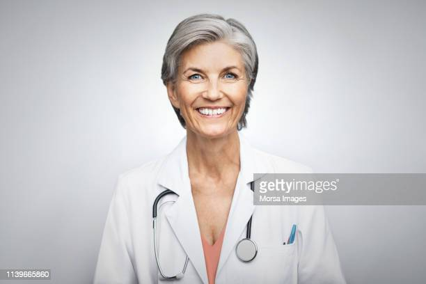senior female doctor smiling on white background - dokter stockfoto's en -beelden