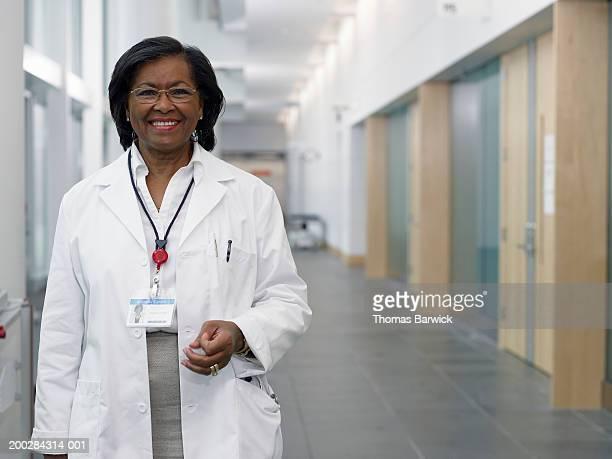 Senior female doctor standing in hospital corridor, smiling, portrait