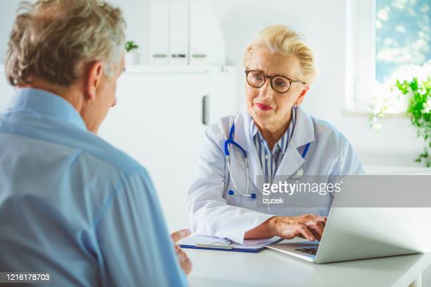 senior female doctor using laptopn in her office - outpatient care stock pictures, royalty-free photos & images