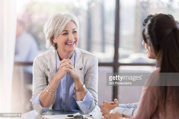 senior female executive smiles during corporate briefing - social grace stock pictures, royalty-free photos & images