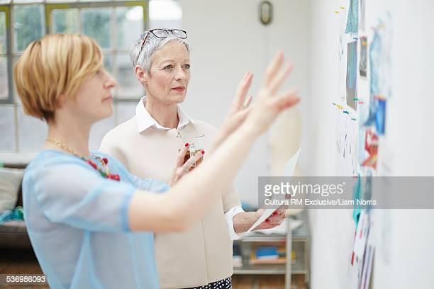 Senior female fashion designer and client explaining ideas
