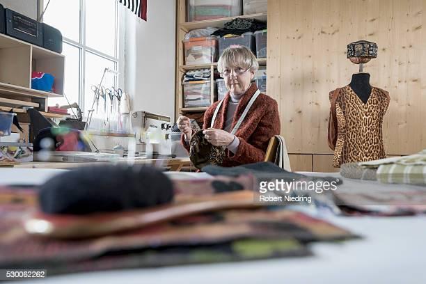 senior female fashion designer stitching cap in workshop, bavaria, germany - 裁縫道具 ストックフォトと画像