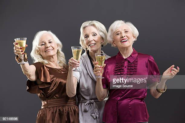 senior female friends toasting with champagne - grey dress stock pictures, royalty-free photos & images