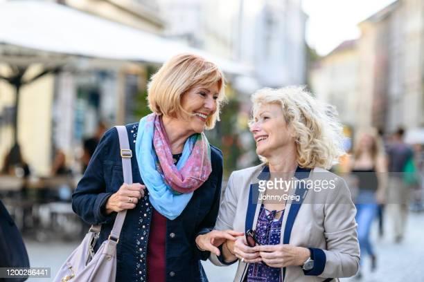 amiche senior che camminano e parlano a lubiana - 55 59 anni foto e immagini stock