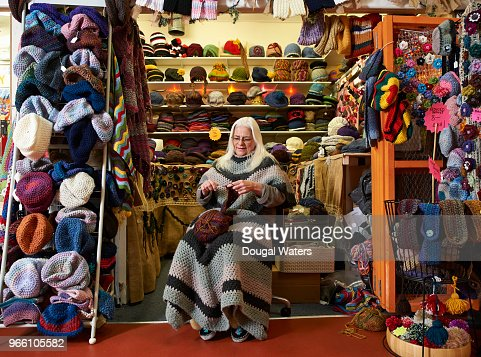 Senior female hat maker working on her hand crafts market stall.
