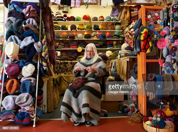 senior female hat maker working on her hand crafts market stall. - multi colored hat stock pictures, royalty-free photos & images