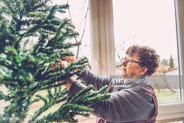 Senior Frau Hausfrau bereitet Weihnachtsbaum auf Balkon, Slowenien, Europa