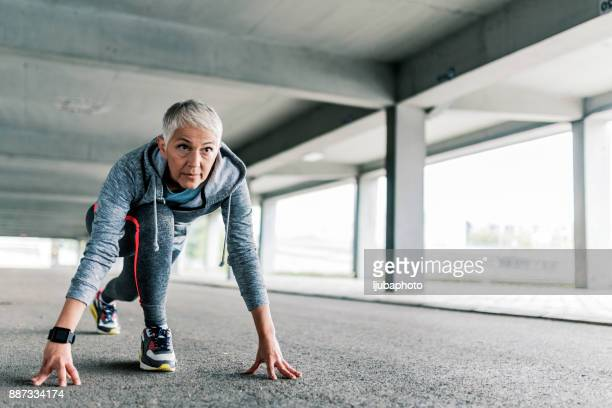 senior female in the starting position to run - warming up stock pictures, royalty-free photos & images