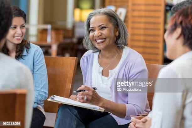 Senior female mental health professional facilitates group therapy session