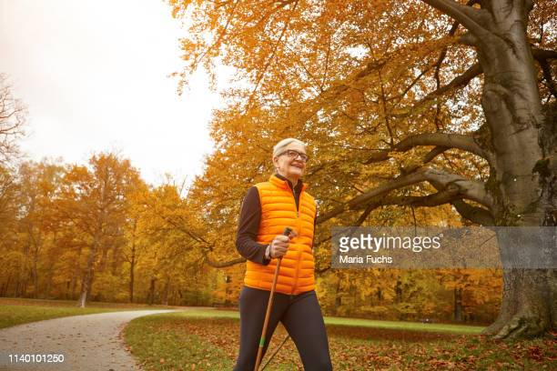 senior female nordic walker striding in autumn park - striding stock pictures, royalty-free photos & images