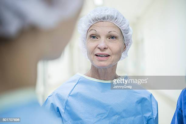 Senior female nurse wearing surgical cap and scrubs
