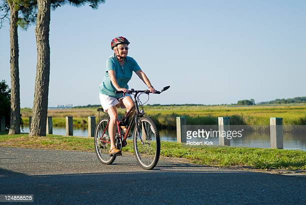 senior female on bicycle - bethany beach stock photos and pictures