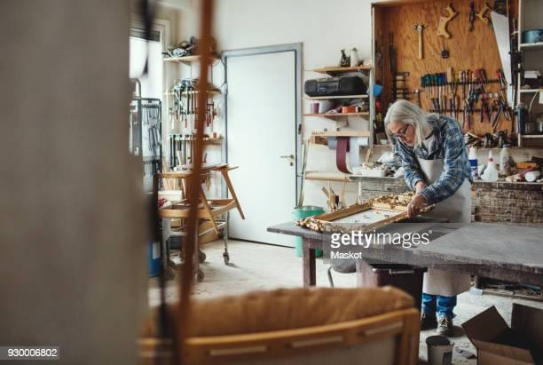 Senior female owner working on carved product at workshop