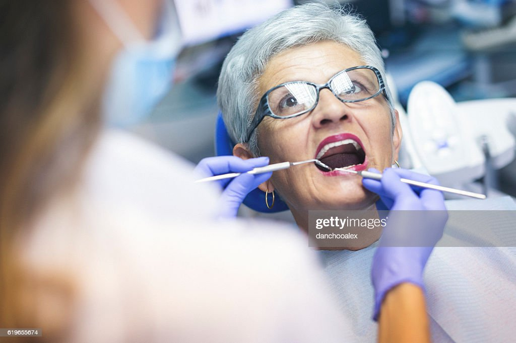 Senior female patient at dentist office : Stock Photo
