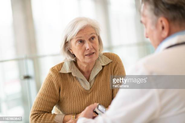 senior female patient at medical consultation - number 2 stock pictures, royalty-free photos & images