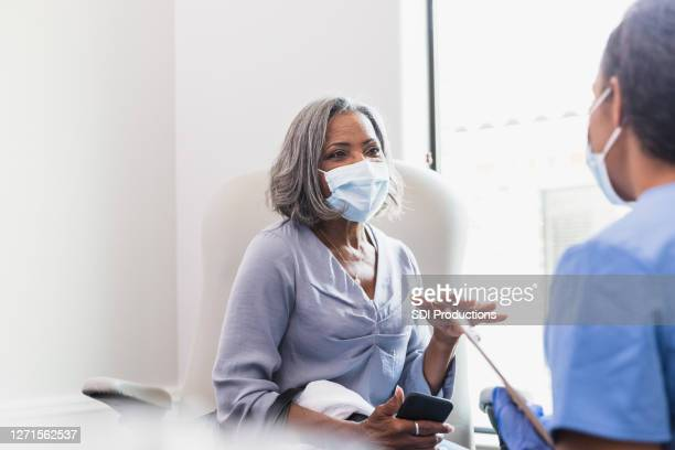 senior female patient talks with healthcare professional - doctor mask stock pictures, royalty-free photos & images